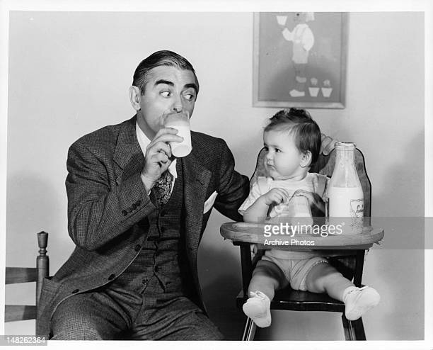 Eddie Cantor sharing milke with Baby Quintanilla in a scene from the film 'Forty Little Mothers' 1940
