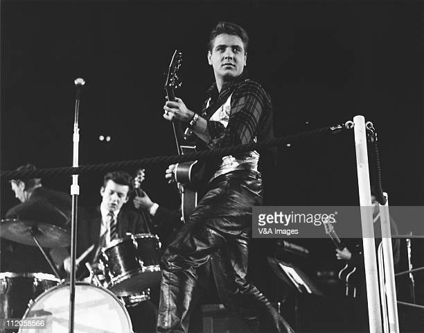 Eddie Cochran performs on stage at NME Poll Winners Party concert, Wembley Empire Pool, with Brian Bennett of the Shadows on drums, 20 February 1960.