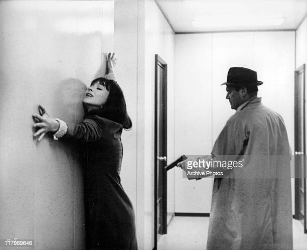 Eddie Constantine pointing a gun towards Anna Karina stretching her arms against the wall in a scene from the film 'Alphaville' 1965