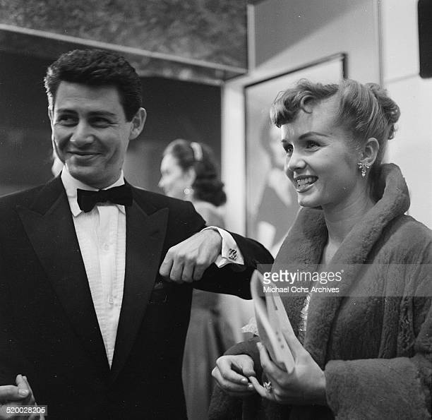 Eddie Fisher and Debbie Reynolds attend the movie premiere of The Country Girl in Los AngelesCA