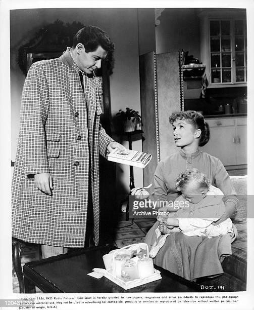 Eddie Fisher offers Debbie Reynolds book on child rearing in a scene from the film 'Bundle Of Joy' 1956