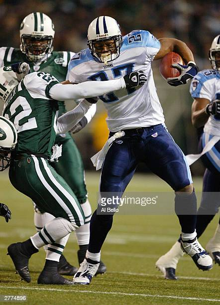 Eddie George of the Tennesee Titans fends off Tyrone Carter of the New York Jets during their game at Giants Stadium on December 1 2003 in East...