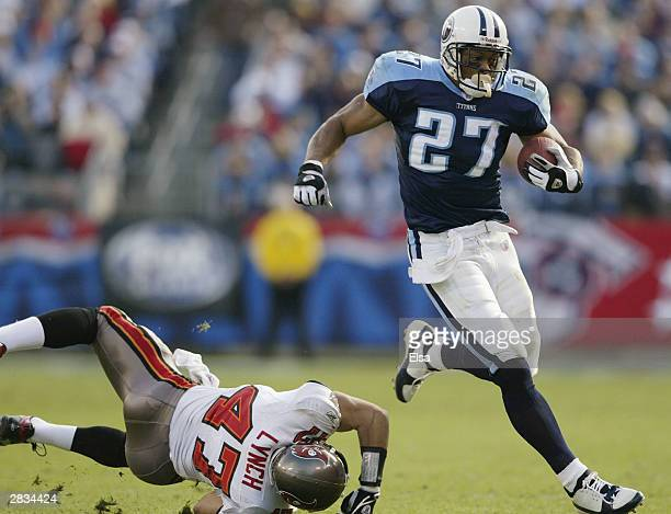 Eddie George of the Tennessee Titans avoids getting tackled by John Lynch of the Tampa Bay Buccaneers on December 28 2003 at The Coliseum in...