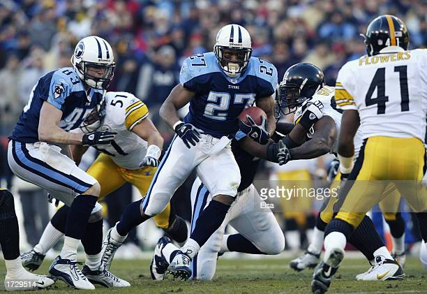 Eddie George of the Tennessee Titans carries the ball against the Pittsburgh Steelers at the Coliseum on January 11 2003 in Nashville Tennessee...