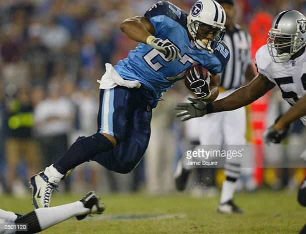 Eddie George of the Tennessee Titans carries the ball against the Oakland Raiders on September 7 2003 at the The Coloseum in Nashville Tennessee The...
