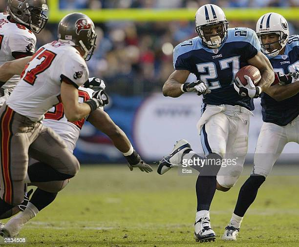 Eddie George of the Tennessee Titans finds the opening in the first half against the Tampa Bay Buccaneers on December 28 2003 at The Coliseum in...