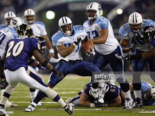 Eddie George of the Tennessee Titans runs the football and looks to get by safety Ed Reed of the Baltimore Ravens in the NFL AFC Wild Card game on...