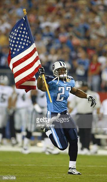 Eddie George of the Tennessee Titans runs with an American flag as he is introduced prior to the game against the Oakland Raiders on September 7 2003...