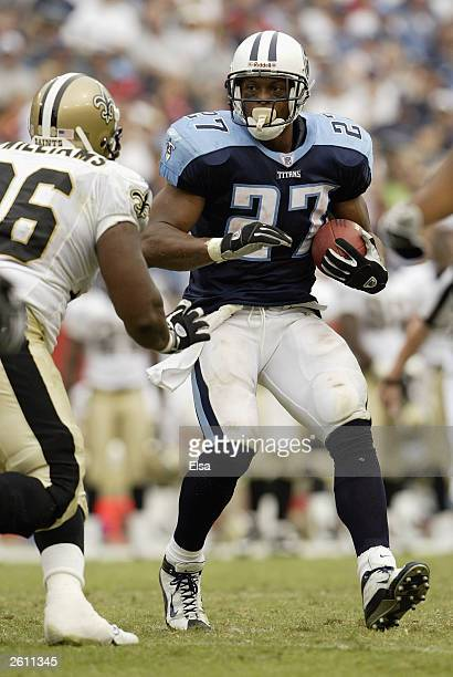 Eddie George of the Tennessee Titans rushes against Melvin Williams the New Orleans Saints on September 21 2003 at The Coliseum in Nashville...