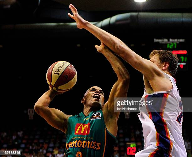 Eddie Gill of the Crocodiles attempts a layup over Daniel Johnson of the 36ers during the round 17 NBL match between the Townsville Crocodiles and...