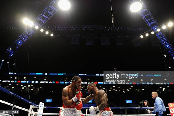 Eddie Gomez punches Daquan Arnett during their super welterweight fight at Barclays Center on January 30 2014 in the Brooklyn borough of New York City