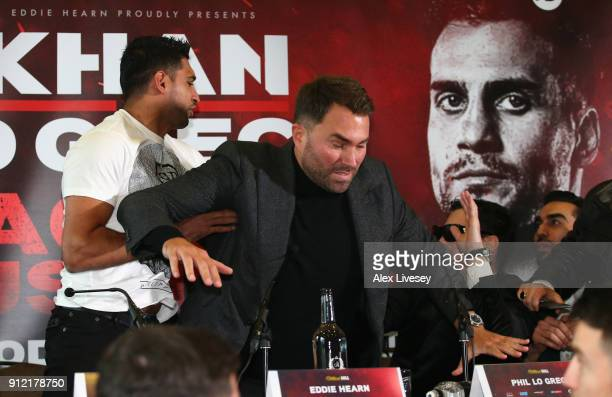 Eddie Hearn gets inbetween Amir Khan and Phil Lo Greco after Amir Khan throws a glass of water at Phil lo Greco during an Amir Khan and Phil Lo Greco...
