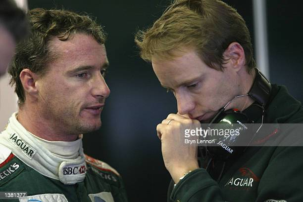 Eddie Irvine of Northern Ireland and Jaguar chats to an engineeer during first practice for the FIA Formula One Italian Grand Prix at the Autodromo...