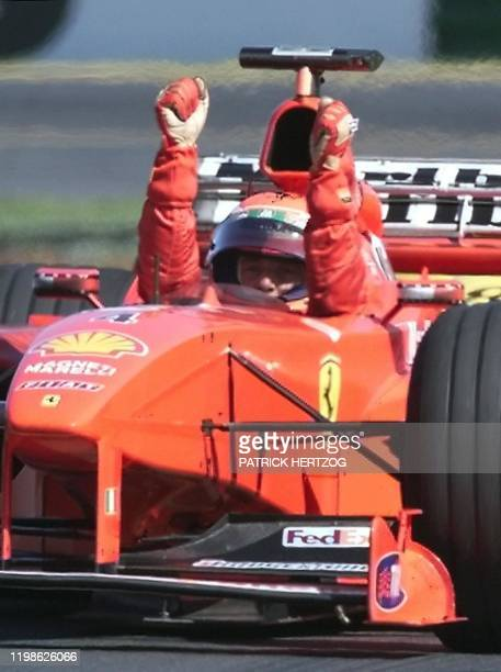 Eddie Irvine of Northern Ireland raises his arms after winning the Australia Formula One Grand Prix in Melbourne 07 March Irvine won the first race...