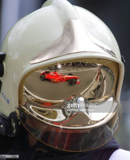 Eddie Irvine's Ferrari is reflected in a Fireman's helmet as he leaves the pits of the racetrack during the first free practice session in Spielberg...