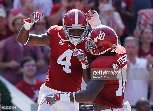 Eddie Jackson of the Alabama Crimson Tide reacts with Reuben Foster after returning an interception for a touchdown against the Western Kentucky...