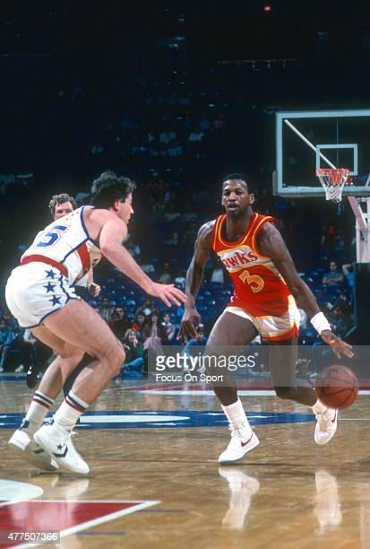 Eddie Johnson of the Atlanta Hawks dribbles past Kevin Grevey of the Washington Bullets during an NBA basketball game circa 1982 at the Capital...