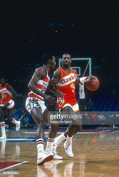 Eddie Johnson of the Atlanta Hawks dribbles the ball while guarded by Don Collins of the Washington Bullets during an NBA basketball game circa 1982...