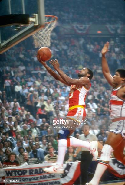 Eddie Johnson of the Atlanta Hawks goes in for a layup in front of Wes Unseld of the Washington Bullets during an NBA basketball game circa 1978 at...