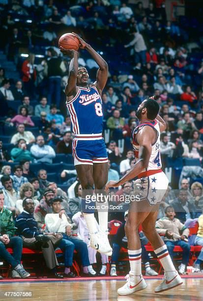 Eddie Johnson of the Kansas City Kings shoots over Greg Ballard of the Washington Bullets during an NBA basketball game circa 1984 at the Capital...