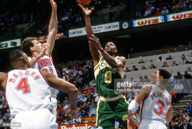 Eddie Johnson of the Seattle Supersonics shoots over Chris Dudley and Drazen Petrovic of the New Jersey Nets during an NBA basketball game circa 1993...