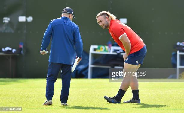 Eddie Jones Head coach of England speaks to Alexander Moon of England during a England Training Session at The Lensbury on October 22 2020 in...