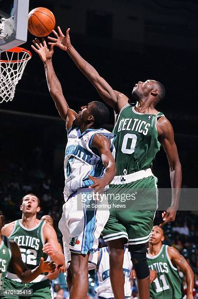Eddie Jones of the Charlotte Hornets lays up a shot against Walter McCarty of the Boston Celtics during the game on October 19 1999 at Charlotte...