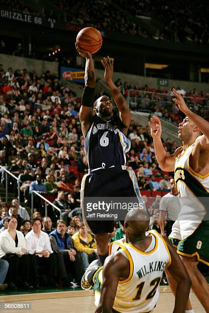 Eddie Jones of the Memphis Grizzlies shoots over Vitaly Potapenko and Damien Wilkins of the Seattle SuperSonics out of his way under the basket on...