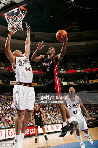 Eddie Jones of the Miami Heat lays one up against Derrick Coleman of the Philadelphia 76ers at the Wachovia Center on December 17 2003 in...