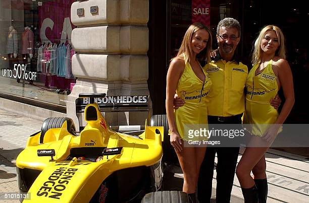 Eddie Jordan team owner of the Jordan F1 Team and F1 glamour girls Michelle Clack and Leah Newman pose on a Jordan F1 car outside the Austin Reed...
