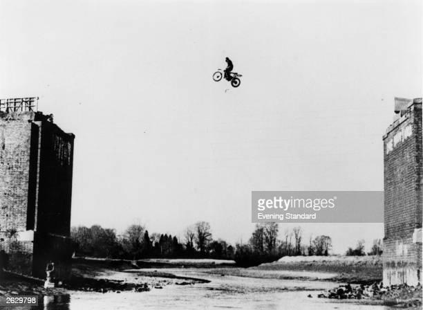 Eddie Kidd English stunt motorcyclist leaps the 80 foot broken span of a railway bridge for the film 'Heavy Metal' at Maldon in Essex Original...