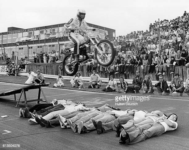 Eddie Kidd the motorcycle stuntman leaps over 10 British disc jockeys before crowds at Brands Hatch Tony Blackburn who is last in line turns his head...