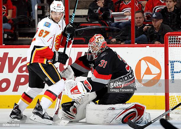 Eddie Lack of the Carolina Hurricanes and Michael Frolik of the Calgary Flames battle for position in the crease during an NHL game at PNC Arena on...