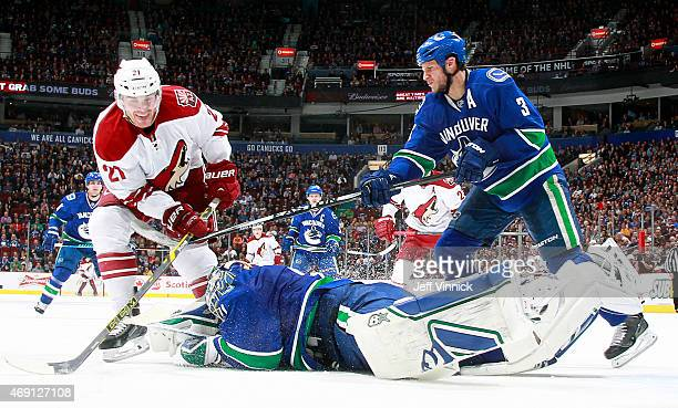 Eddie Lack of the Vancouver Canucks dives to smother the puck on the stick of Jordan Szwarz of the Phoenix Coyotes with Kevin Bieksa of the Canucks...
