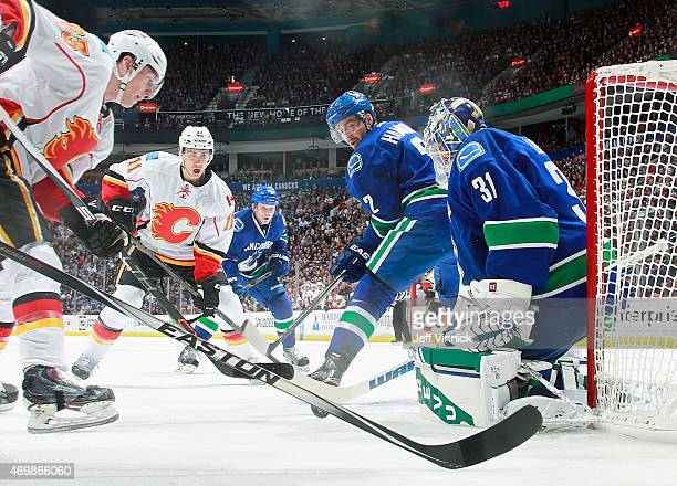 Eddie Lack of the Vancouver Canucks makes a save surrounded by Sam Bennett and Mikael Backlund of the Calgary Flames and Dan Hamhuis of the Canucks...