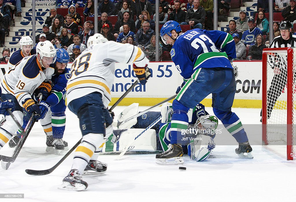 Eddie Lack #31 of the Vancouver Canucks reaches between the legs of Alexander Edler #23 as Cory Conacher #88 of the Buffalo Sabres eyes the puck during their NHL game at Rogers Arena March 23, 2014 in Vancouver, British Columbia, Canada. Vancouver won 4-2.