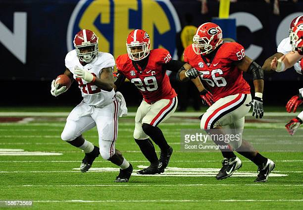 Eddie Lacy of the Alabama Crimson Tide carries the ball against Garrison Smith and Jarvis Jones of the Georgia Bulldogs during the SEC Championship...