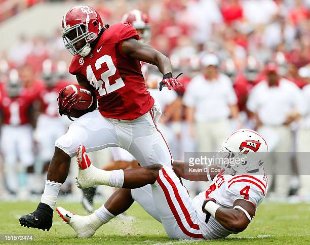 Eddie Lacy of the Alabama Crimson Tide tries to break a tackle by Andrew Jackson of the Western Kentucky Hilltoppers at BryantDenny Stadium on...