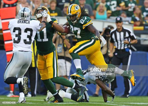 Eddie Lacy of the Green Bay Packers runs for a first down during the first quarter of their preseason game against Oakland Raiders at Lambeau Field...