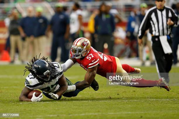 Eddie Lacy of the Seattle Seahawks is tackled by Eli Harold of the San Francisco 49ers at Levi's Stadium on November 26 2017 in Santa Clara California