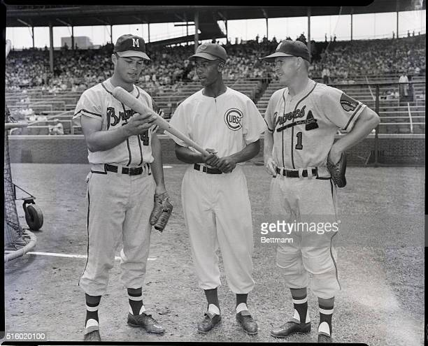 Eddie Mathews and Del Crandall both of the Milwaukee Braves check out the bat of Chicago Cubs star shortstop Ernie Banks All three were chosen to...