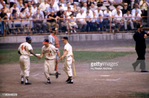 Eddie Mathews of the Milwaukee Braves is congratulated by the batboy and his teammate Hank Aaron after hitting a homerun during an MLB game against...