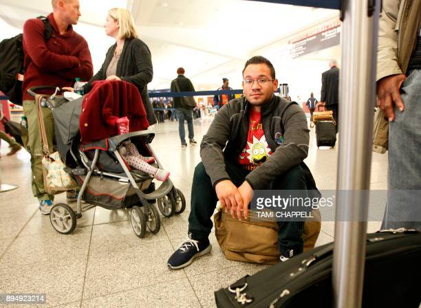 Eddie Medina of Puerto Rico sits on his luggage as he waits in line at the Delta Airlines counter the day following a power outage caused by a fire...