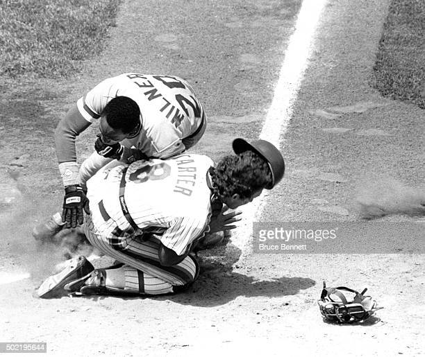 Eddie Milner of the Cincinnati Reds crashes into catcher Gary Carter of the New York Mets during their game circa 1986 at Shea Stadium in Flushing,...