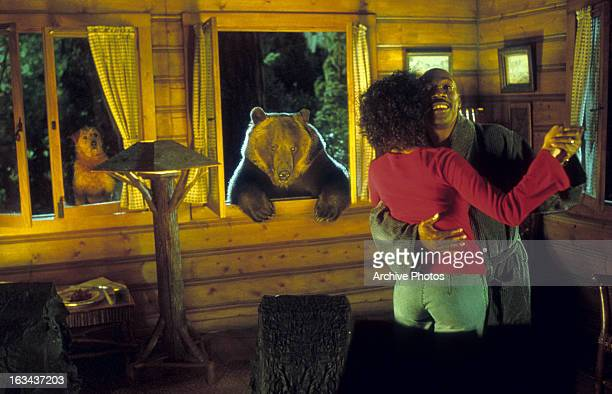 Eddie Murphy dancing with woman while bear and dog watch in a scene from the film 'Dr. Dolittle 2', 2001.