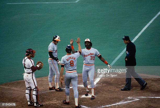 Eddie Murray of the Baltimore Orioles crosses home plate and is congratulated by Cal Ripken Jr with a highfive during the World Series against the...