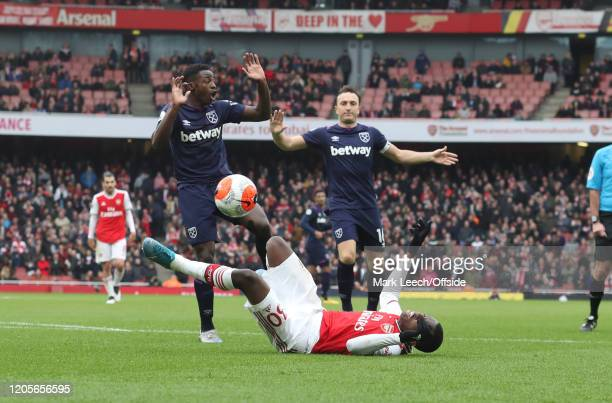 Eddie Nketiah of Arsenal falls after a challenge by Jeremy Ngakia of West Ham in the penalty area during the Premier League match between Arsenal FC...