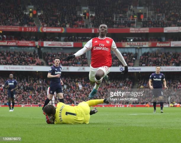 Eddie Nketiah of Arsenal jumps over West Ham goalkeeper Lukasz Fabianski during the Premier League match between Arsenal FC and West Ham United at...