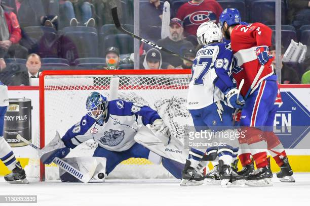 Eddie Pasquale of the Syracuse Crunch about to make a split save while Alexandre Grenier of the Laval Rocket and Mitchell Stephens look on at Place...