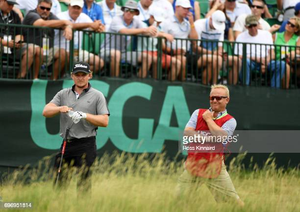 Eddie Pepperell of England and caddie William Todd Clarkson wait to play his shot from the first tee during the third round of the 2017 US Open at...